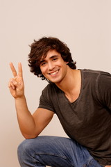 Smiling guy making peace sign with hand