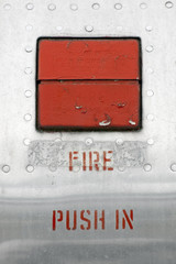 old fire emergency button embedded in a metal panel
