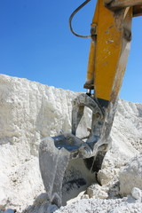 Caterpillar excavator jib in chalk pit against a blue sky