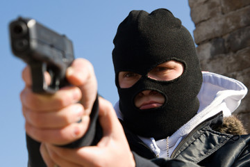 Criminal in mask aiming his target