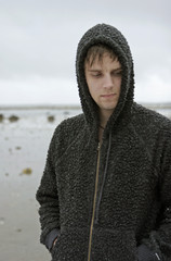 Hooded man at the beach