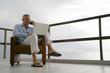 Homme sur une terrasse téléphonant devant un ordinateur portable