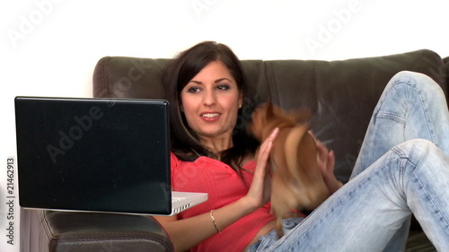 Laughing woman and her dog using a laptop sitting on sofa