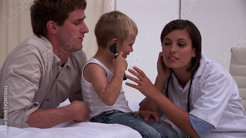 Blond little boy and his father playing with a doctor