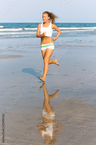 Slim girl running along the beach