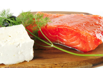 pink smoked salmon on wooden plate with white cheese