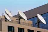Four Satellite Dishes on Building Rooftop poster