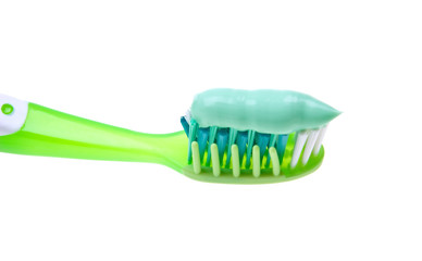 Close-up of a toothbrush with paste isolated on white