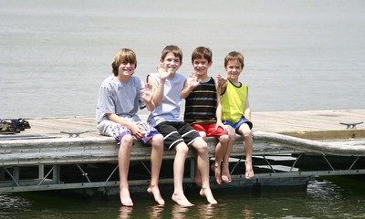 Boys Waving Sitting on the Dock