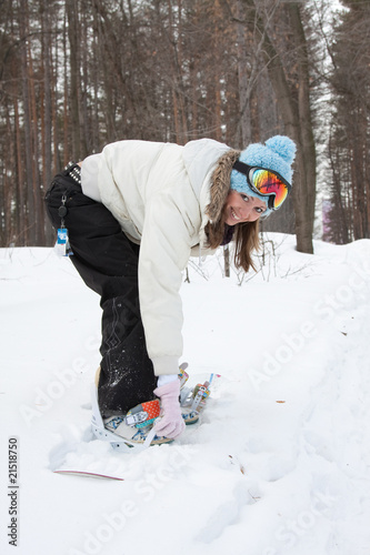 Female snowboarder adjusting bindings