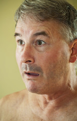 Mature naked man with exaggerated startled expression on face