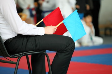 judge at competitions holds a red and dark blue flag
