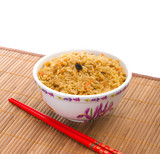 Bowl of cooked rice with chopsticks on bamboo napkin