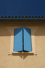 blue shutters on peach wall