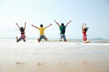 friends jumping togehter on beach