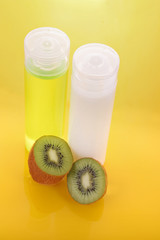 Cosmetic bottles and kiwi on yellow