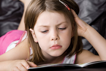 Young Child Reading her Book on the Sofa