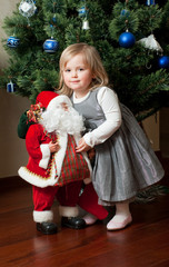 Cute little girl with toy Santa Claus