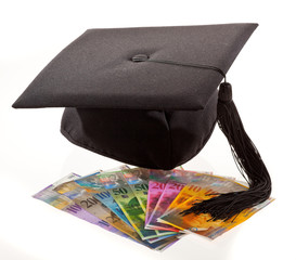 Mortarboard and Swiss francs. Education costs.