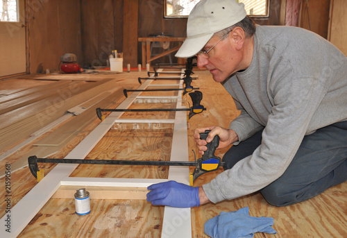 Carpenter adjusting clamp on exterior trim assembly