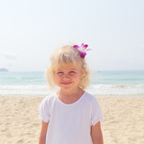 Beautiful little girl on the beach with the orchid