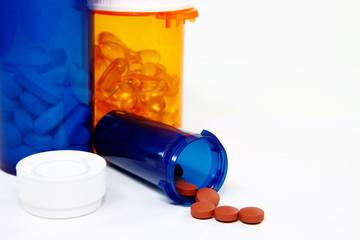 three pill bottles, one spilling pills