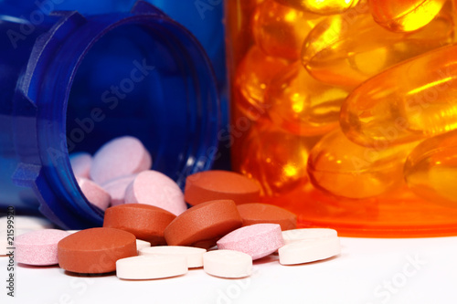 macro view of pill bottle spilling a variety of pills