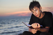 teenager boy reads book sitting on beach in evening