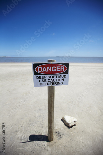 danger and caution sign for deep mud on a beach