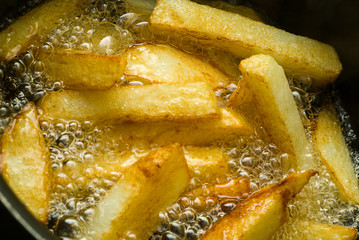 Extreme Macro of chips/fries cooking in a pan.