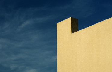 Background: yellow wall and cloudy blue sky
