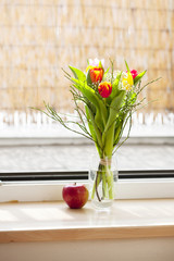 spring bouquet with tulips and an apple