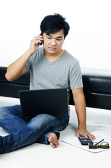 Casual young man talking on cellphone while using laptop