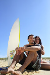 Couple de surfeur assis sur le sable