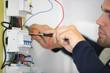 Portrait d'un électricien travaillant sur un compteur électrique - 21637923