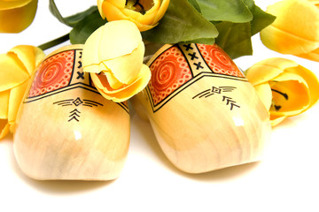 Dutch wooden shoes and silk tulips over white background