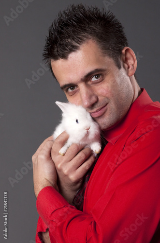Handsome young man holding baby rabbit
