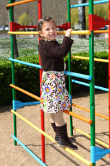 Young girl climbing up a frame in a children's playground
