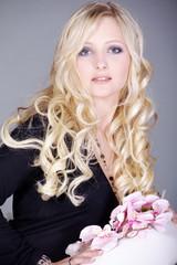 Blonde Frau mit Orchidee verliebt blickend