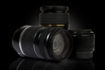 three digital slr camera lenses in black background
