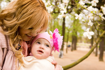 Beautiful young mother and baby daughter having fun outdoors