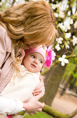 Beautiful young mother with her baby daughter outdoors at spring
