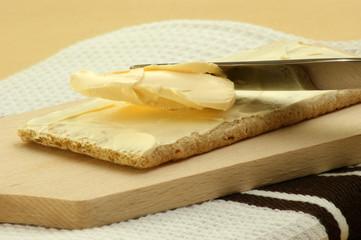 Knäckebrot wird mit Butter bestrichen