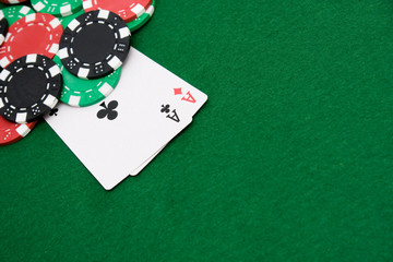 Two aces and gambling chips on green casino felt background