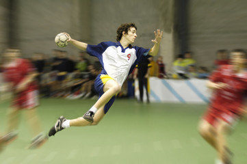 young handball player on a match jumping to score a goal