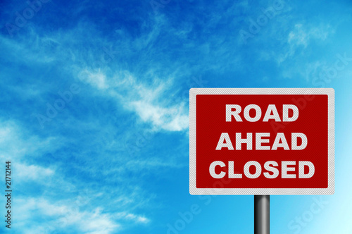 road ahead closed sign against blue sky