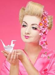 Beautiful geisha holding origami bird