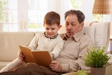 Grandfather reading book to grandson poster