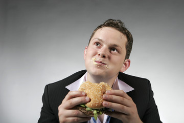 Happy businessman eating junk food