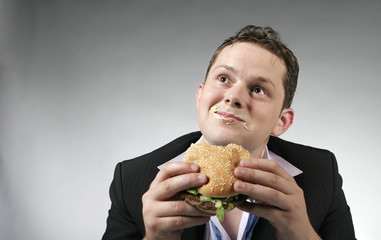 Young businessman is enjoying a hamburger for lunch